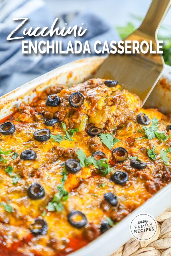 Spatula lifting out a piece of layered zucchini beef enchilada casserole
