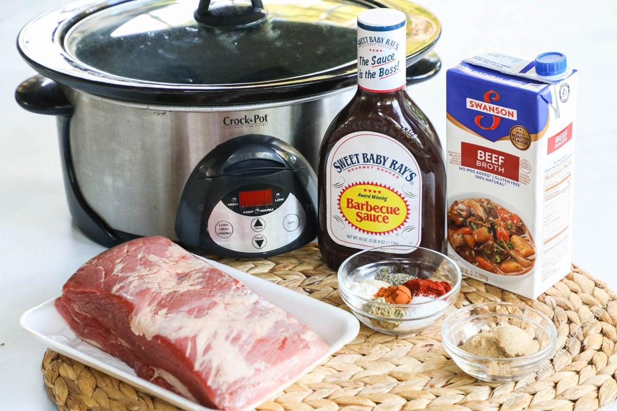 Ingredients for making Slow Cooker Brisket including beef brisket, BBQ sauce, broth, spices and crock pot