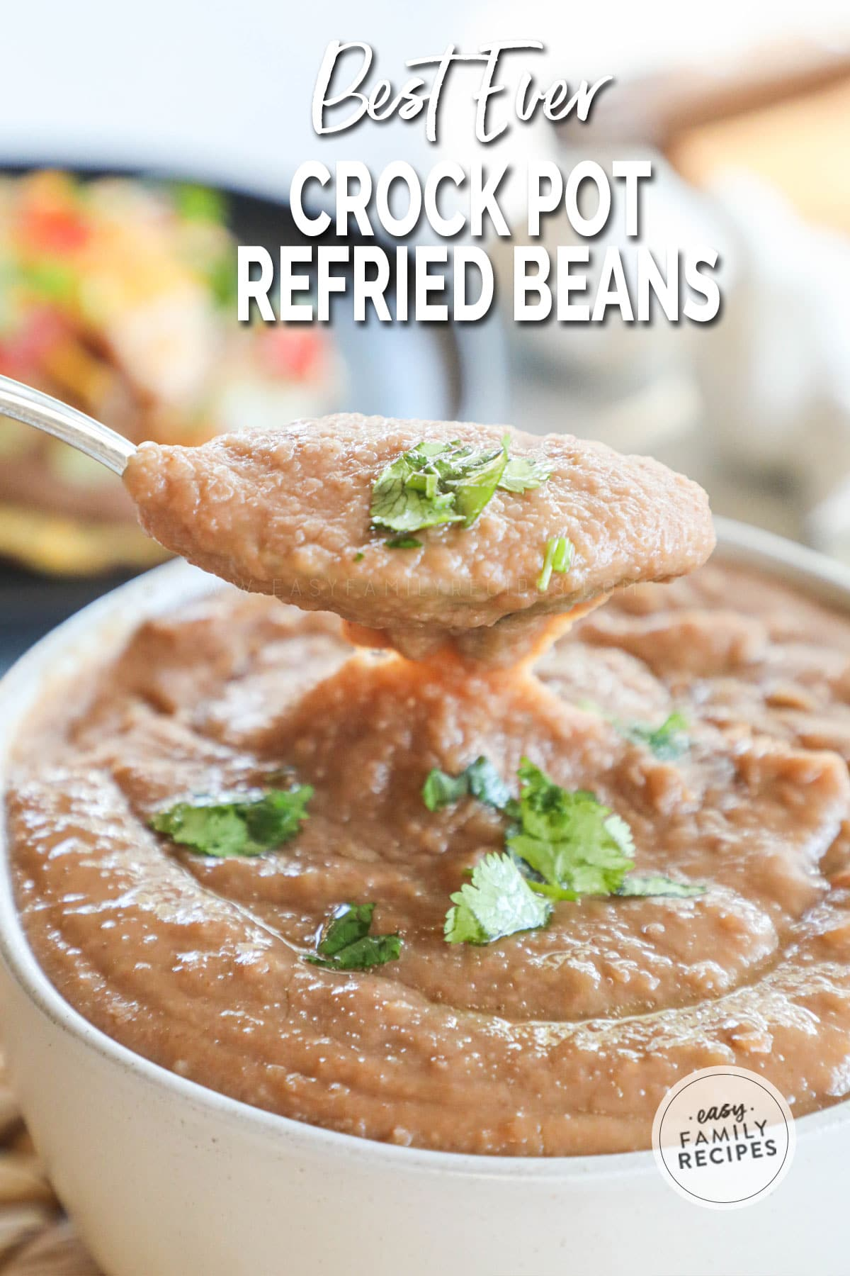 Lifting a spoon full of crock pot refried beans out of the serving bowl