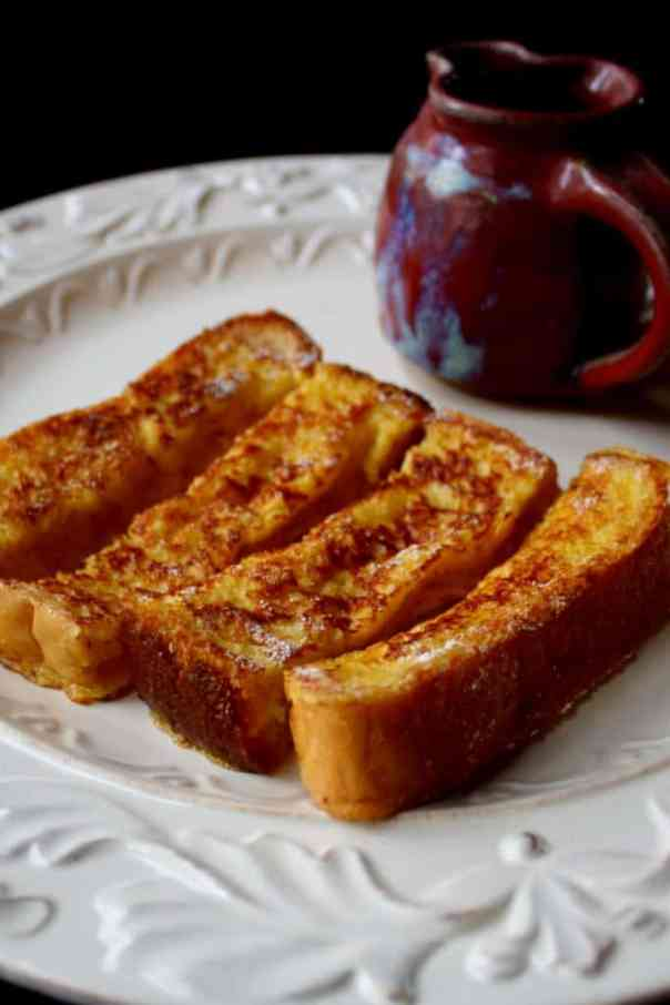 Eggnog French Toast Sticks on plate with cup of syrup