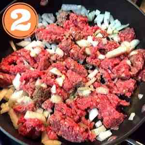 raw ground beef and onions in skillet