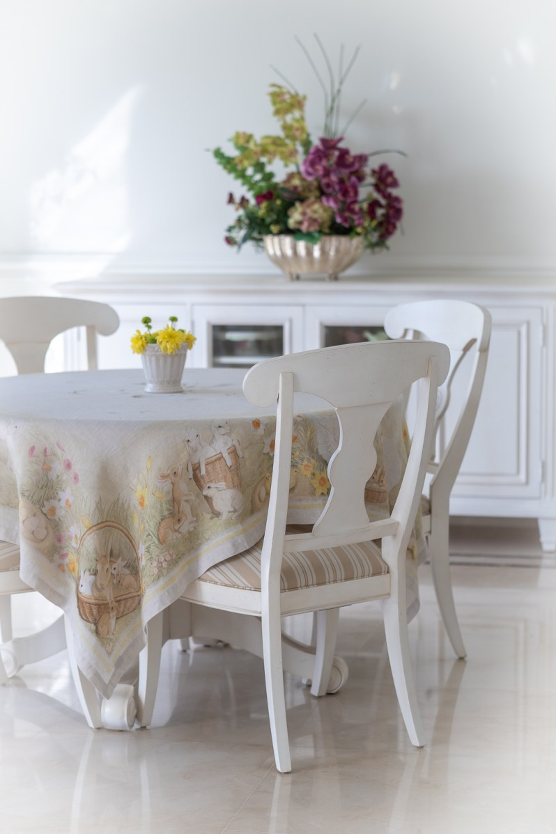 Breakfast nook spring decoration with flowers and Easter theme table cloth.