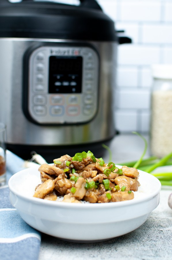 bourbon chicken in a white bowl in front of an instant pot