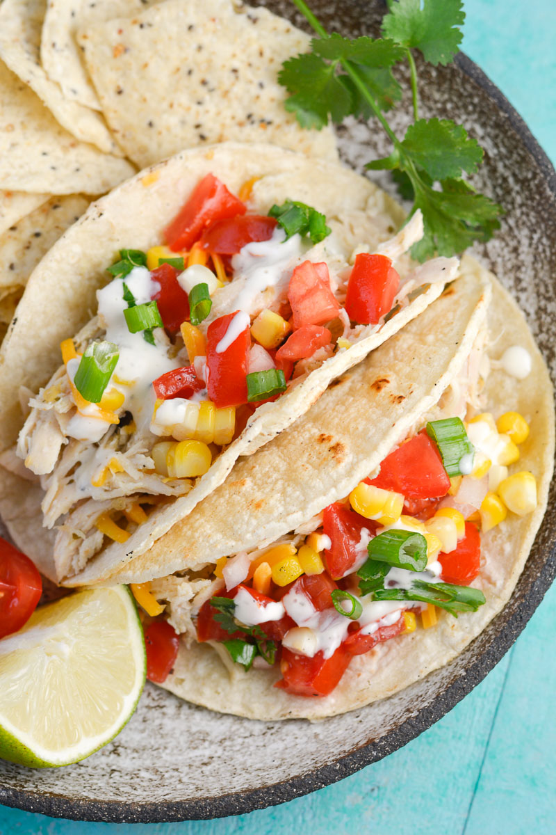 These Slow Cooker Chicken Tacos are seasoned with salsa verde, ranch and lime juice! This zesty crock pot chicken is perfect for tacos, quesadillas and more!