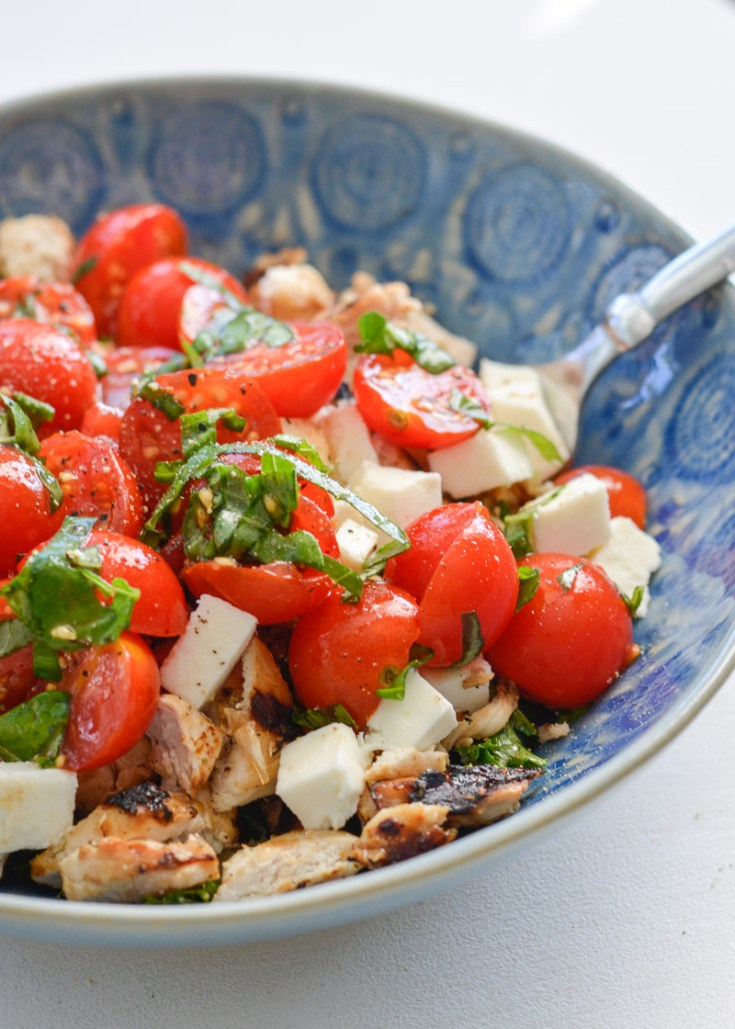 Chicken caprese salad in a blue bowl