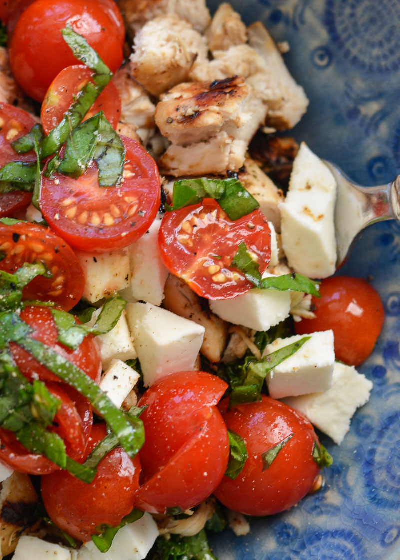 This Chicken Caprese Salad is packed with nutrients and flavor! Chicken, tomatoes, mozzarella, basil and a drizzle of balsamic vinegar dressing all top tender kale in this delicious, fresh dish.