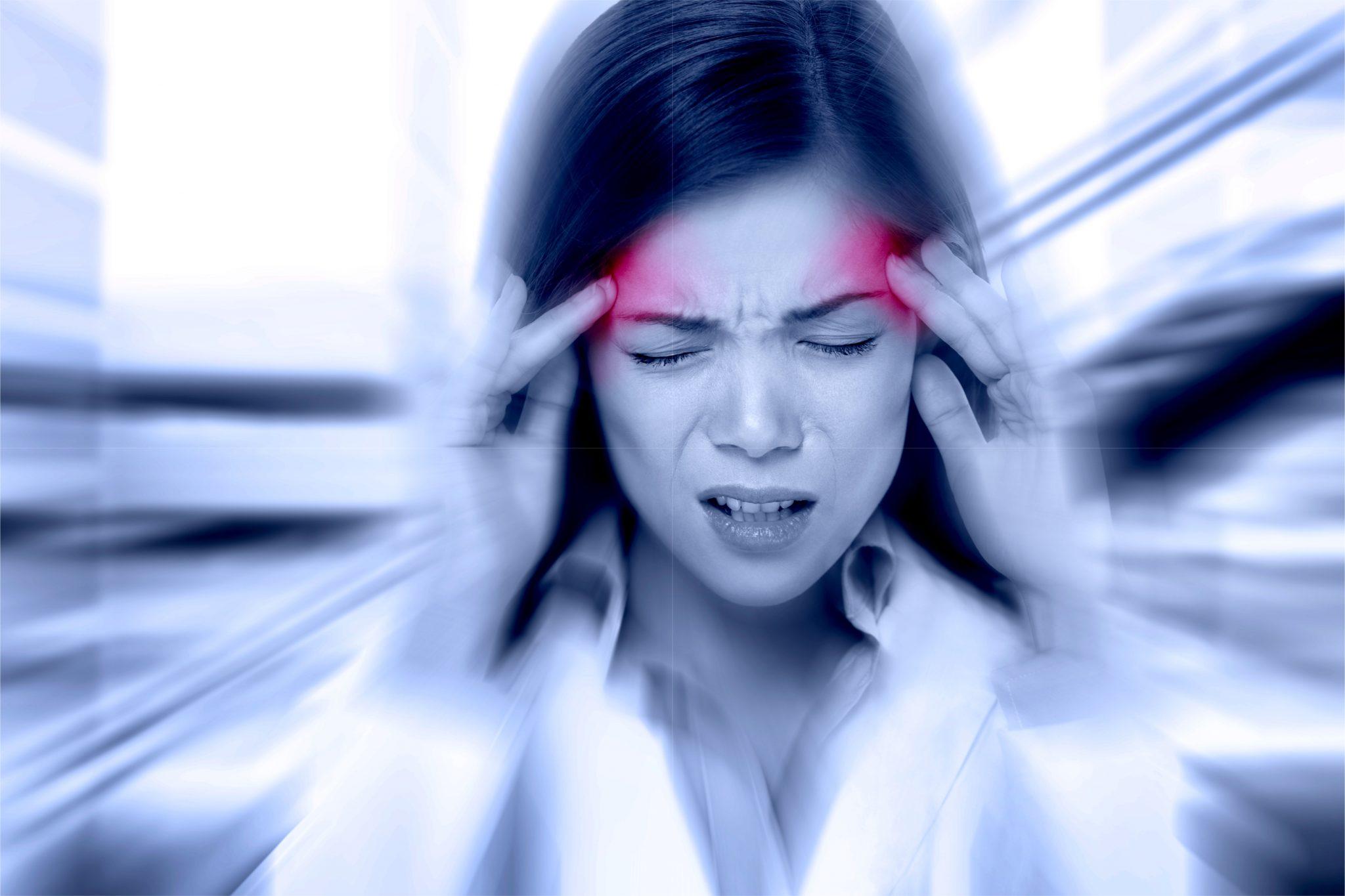 頭痛で頭を抑えている女性