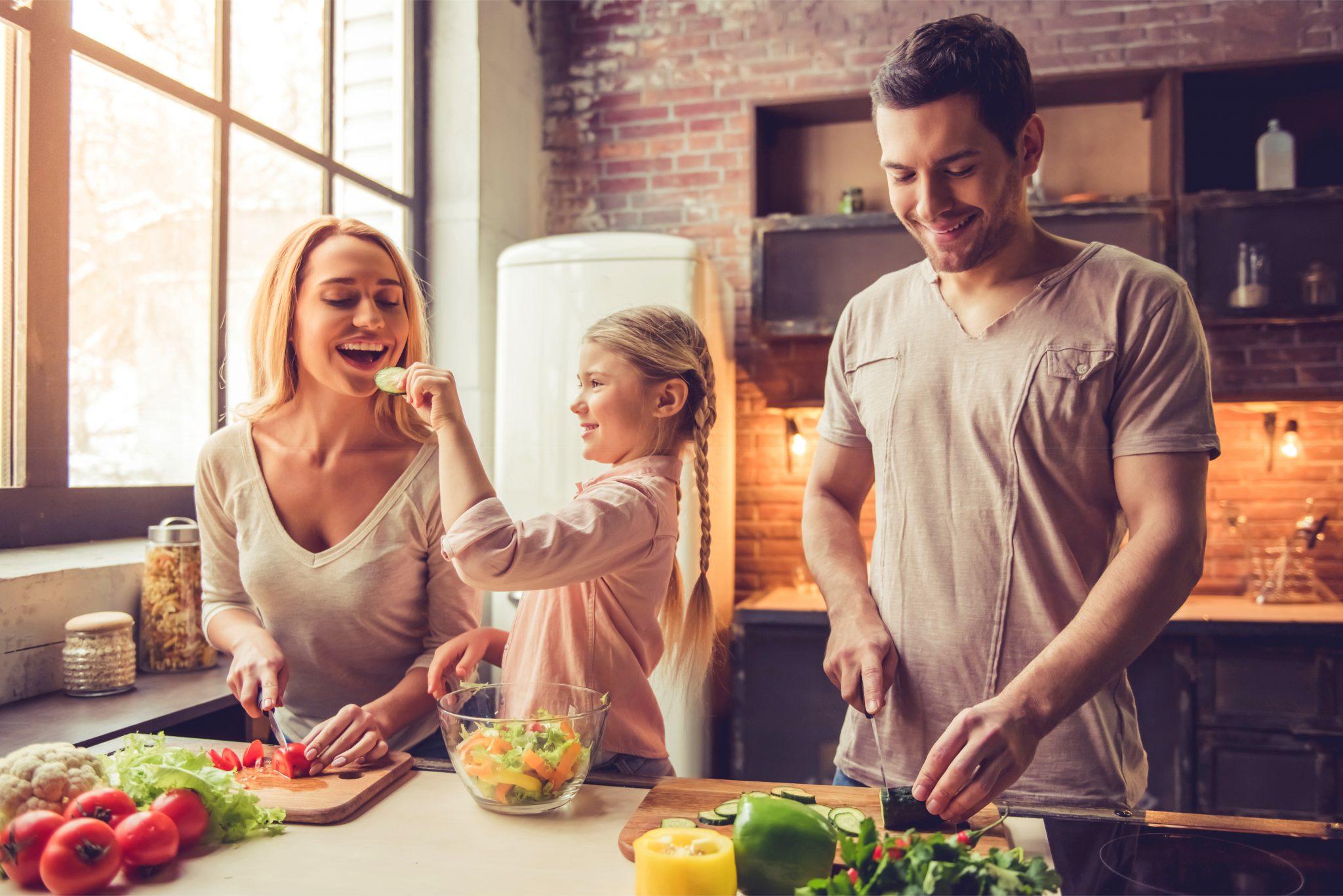 キッチンで家族3人で料理している