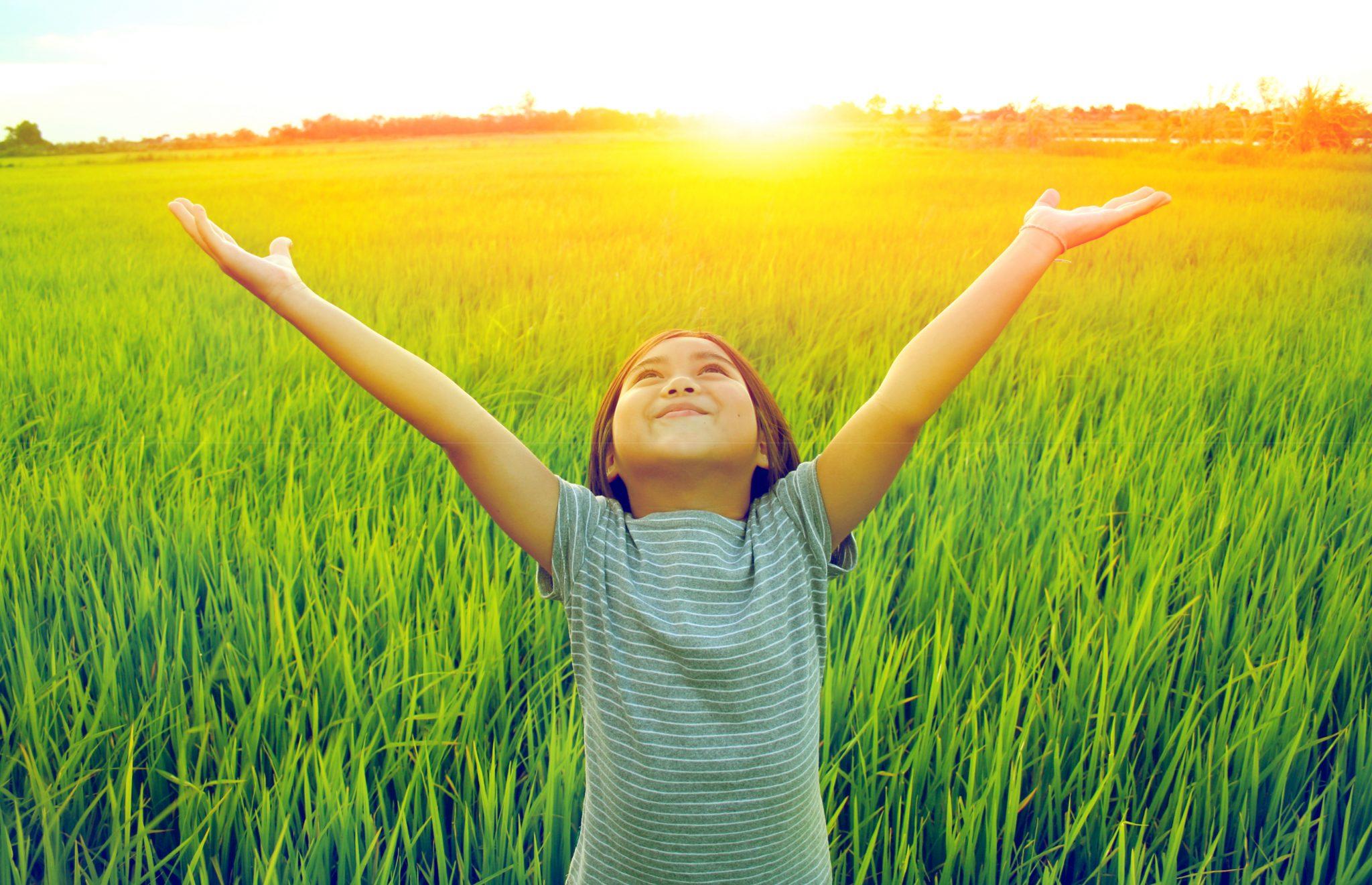 田んぼの前で両手を挙げている子ども