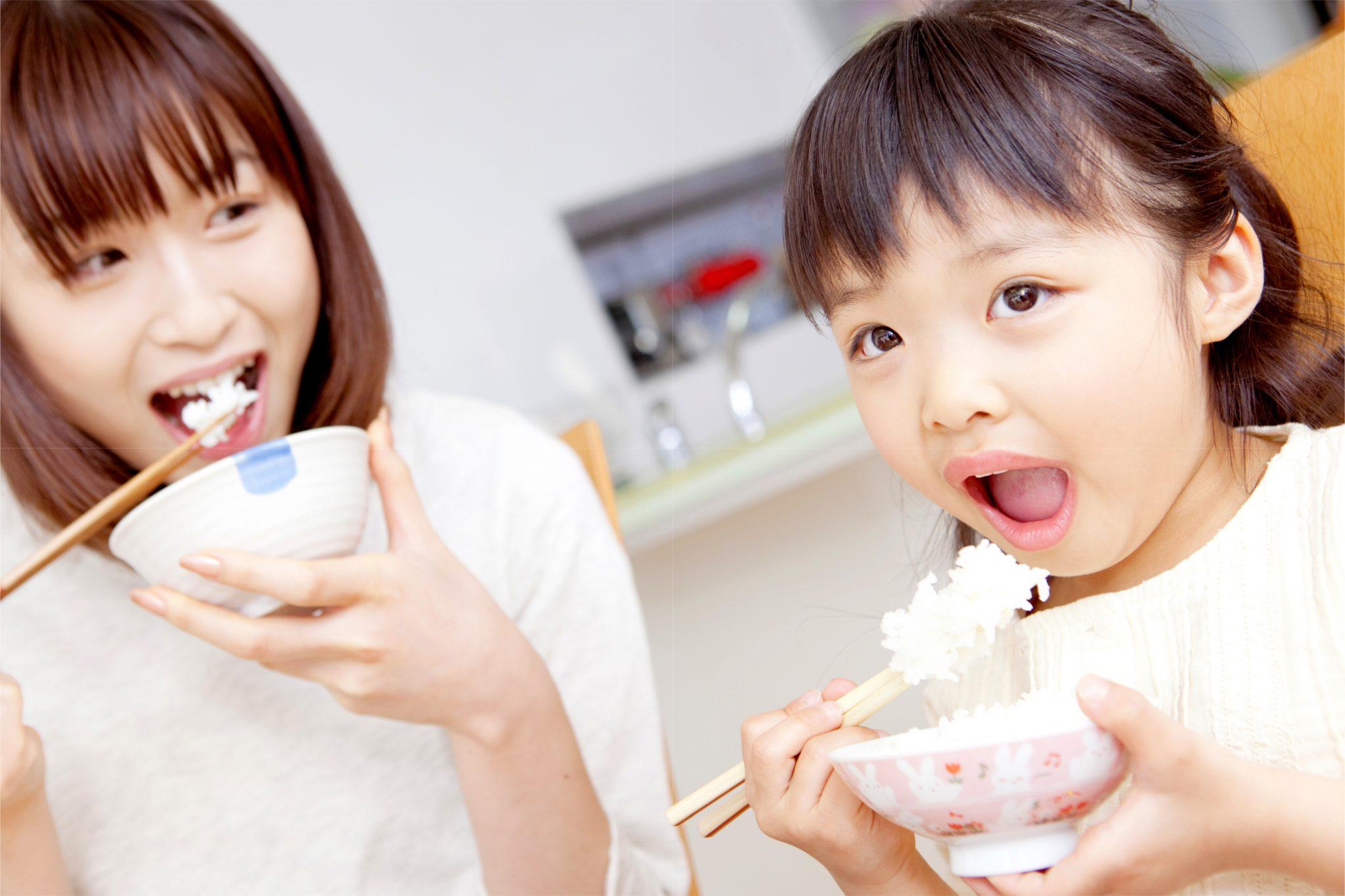 お米を食べているお母さんと娘