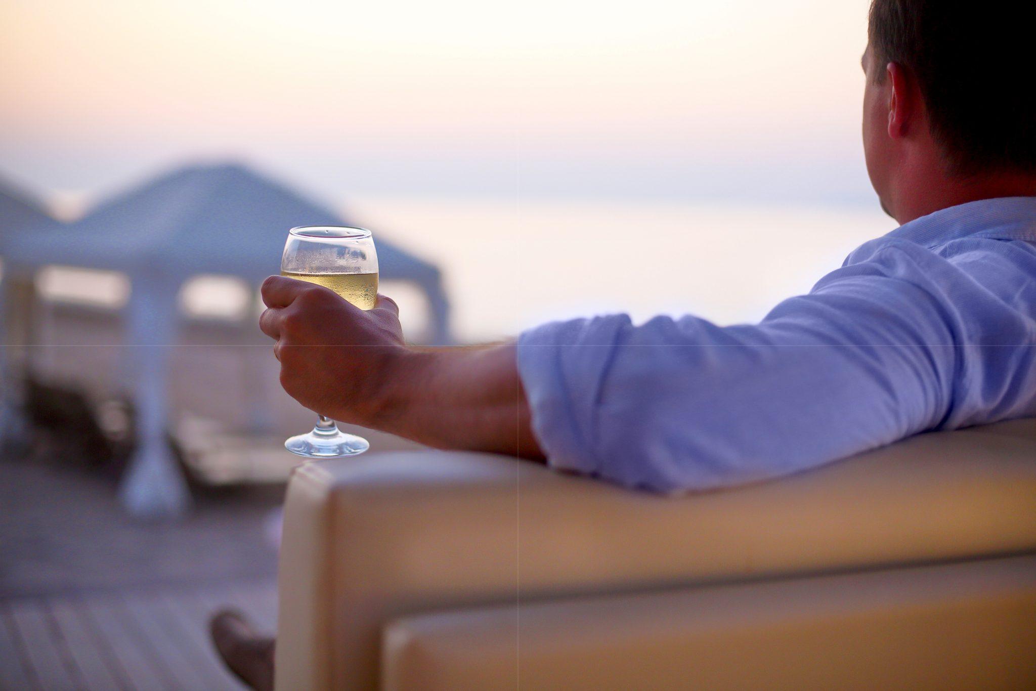 ソファでリラックスしながらお酒を嗜む男性