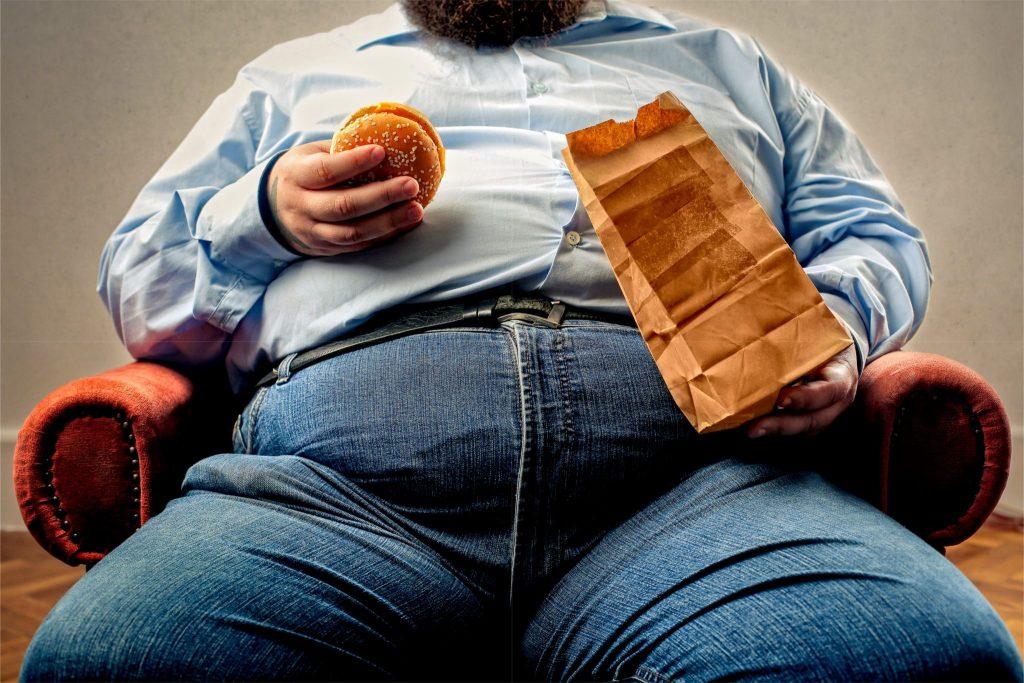 太った男性がハンバーガーを持ってソファに座っている