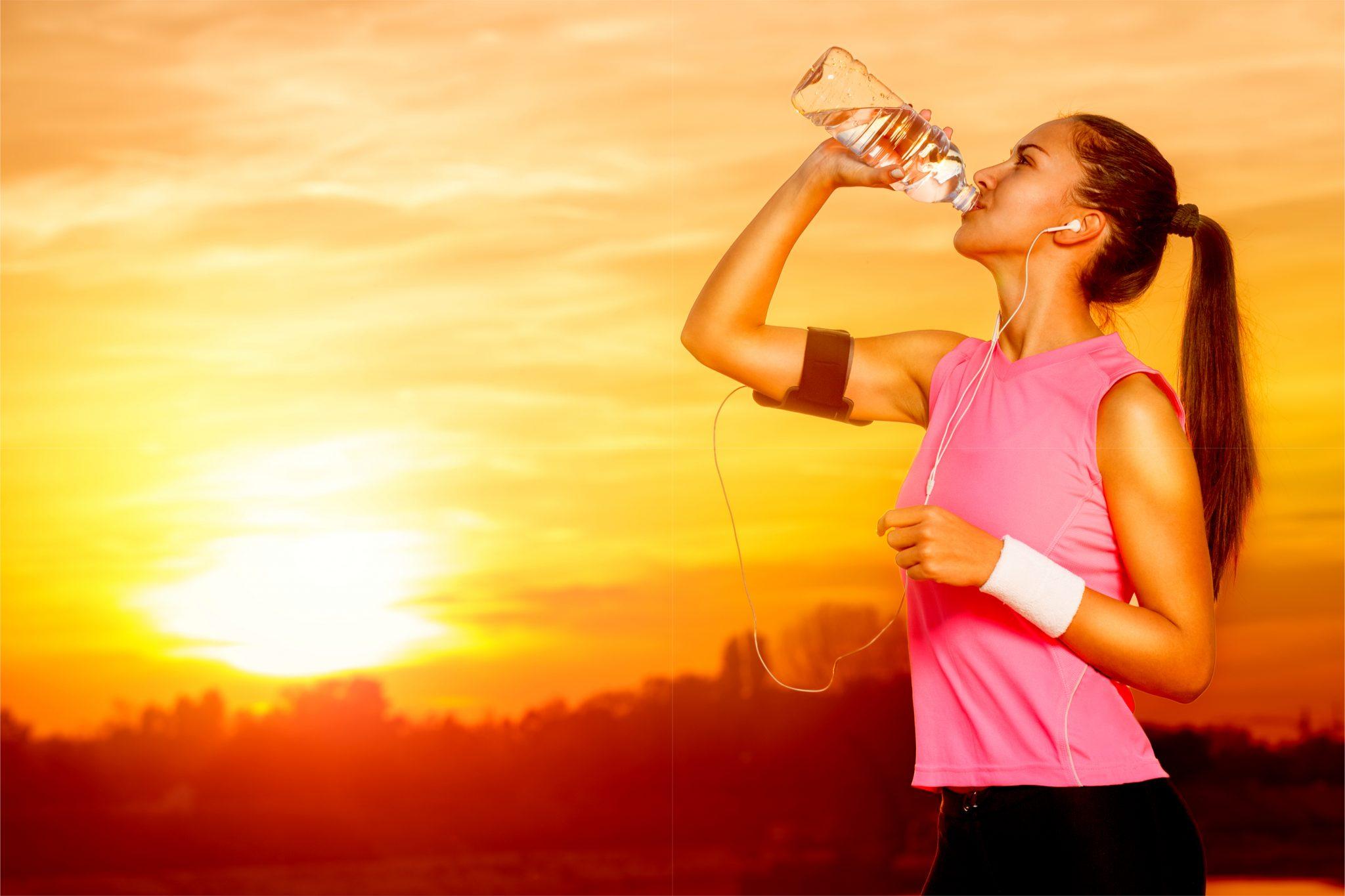 夕日を背景に水分補給している女性
