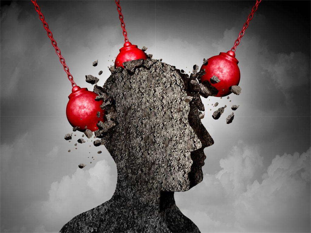 頭痛を石でできた顔と鉄球を使って表現している絵