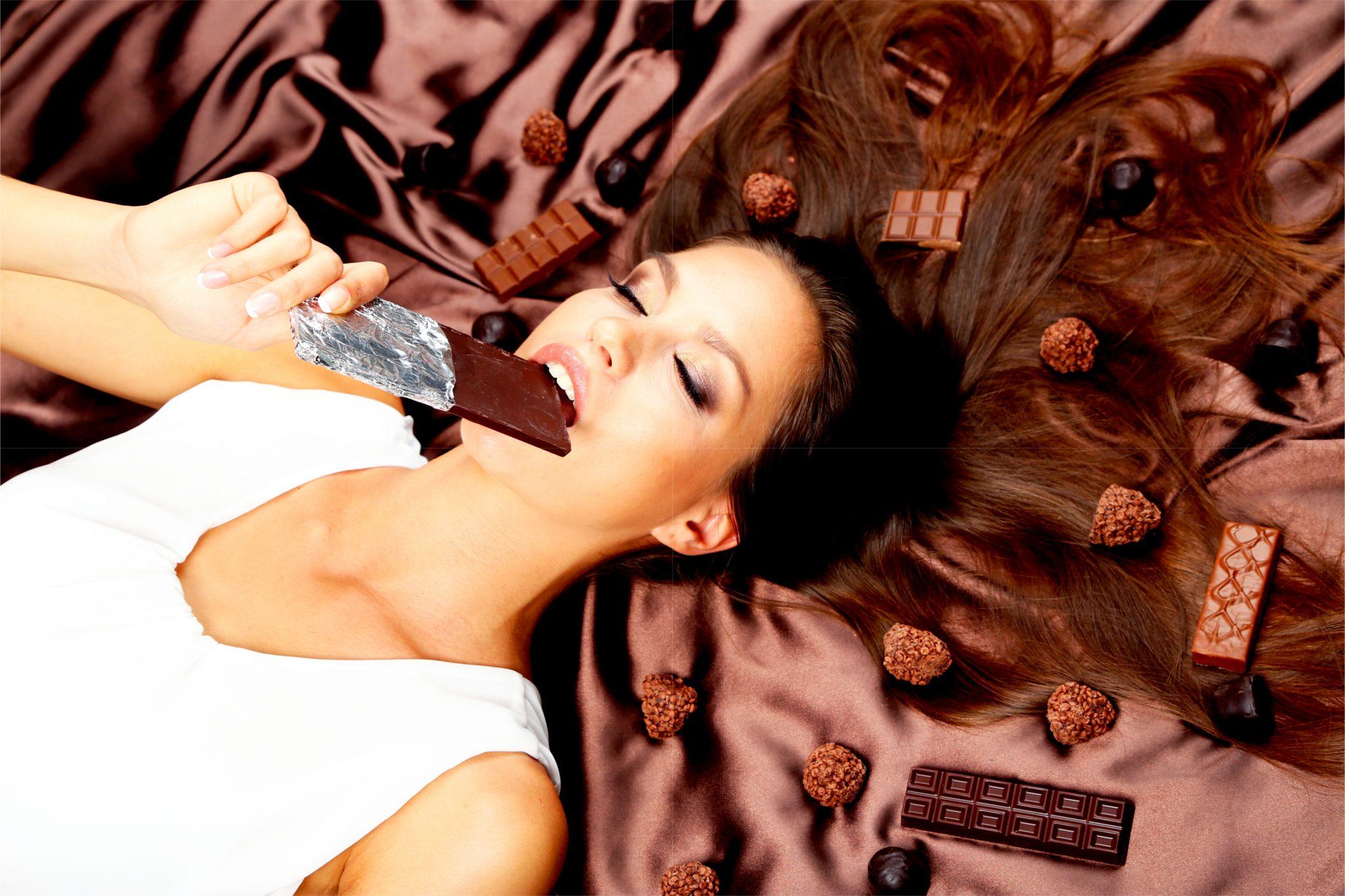チョコレートを横になって食べている細身の女性
