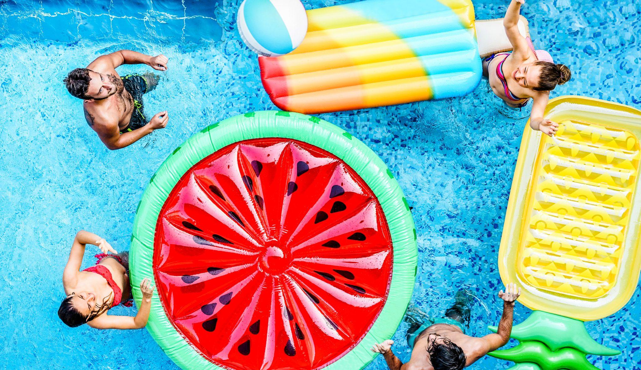 スイカの浮き輪を使ってプールで遊んでいる人たち