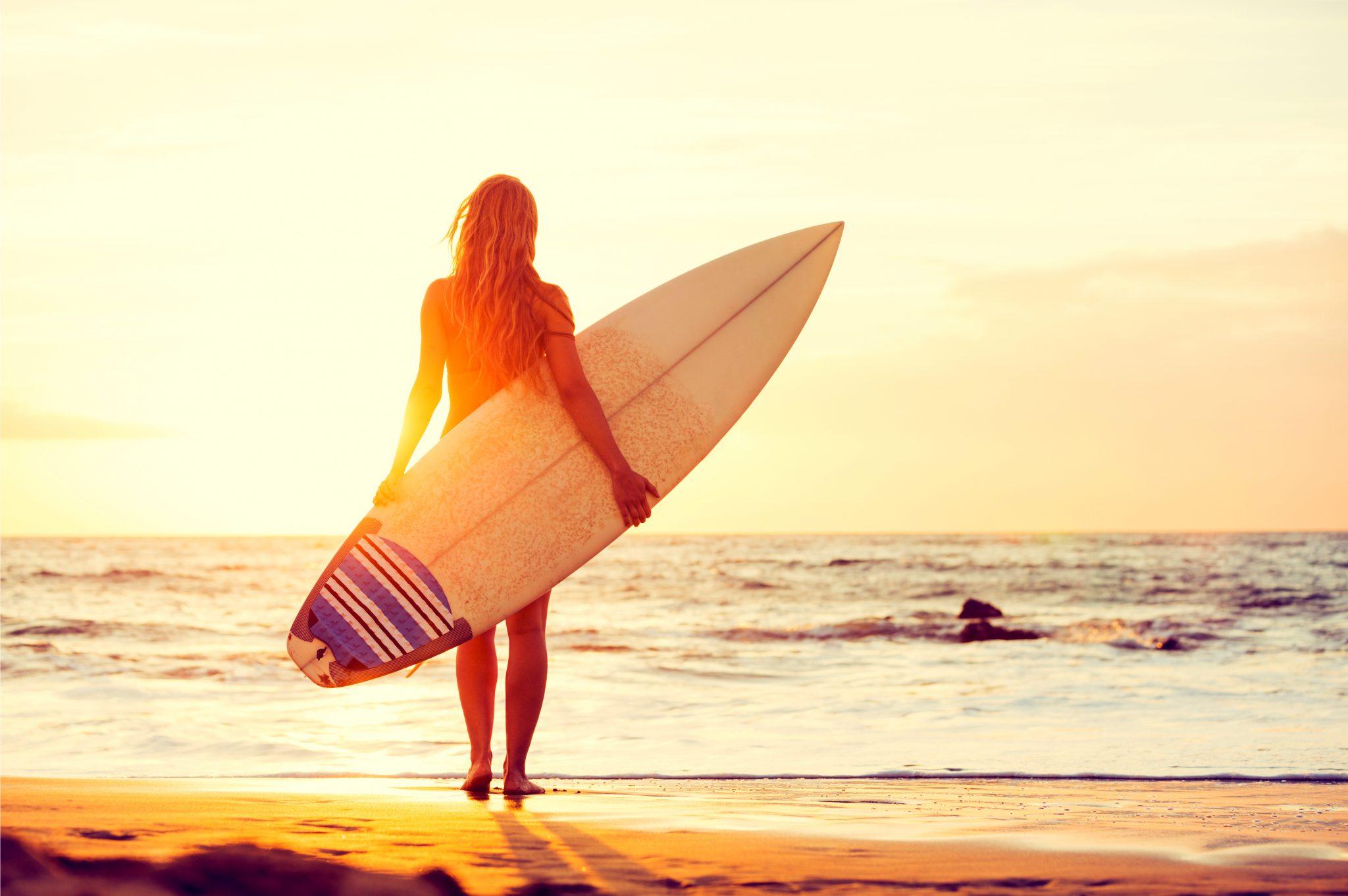 サーフボードを持って夕焼けを見ている女性