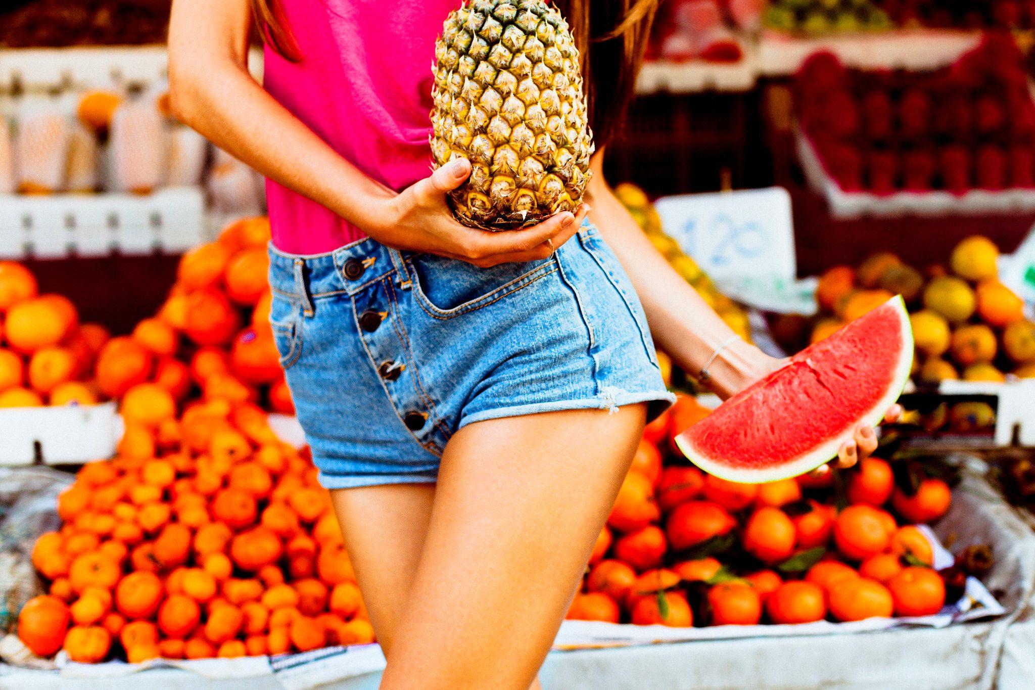 スイカとパイナップルを持っている女性