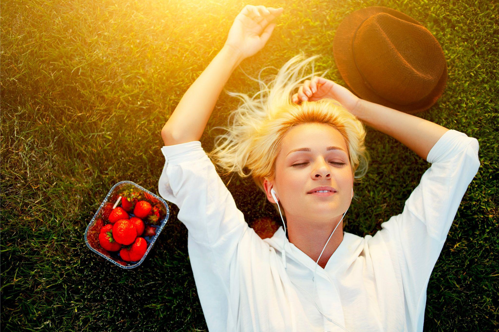芝生で寝っ転がりながらイチゴを食べている女性
