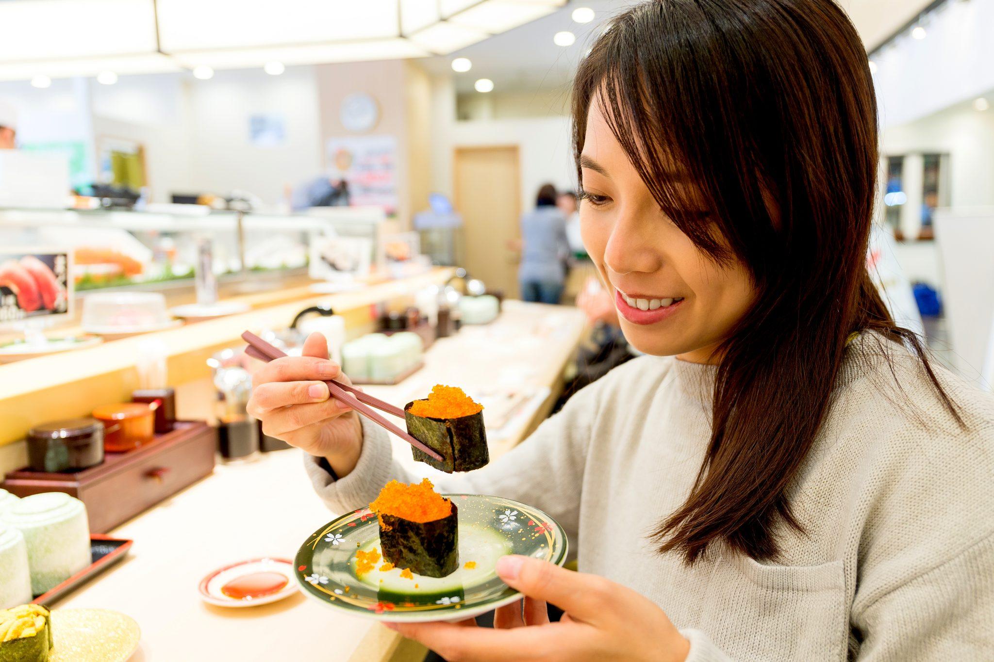 回転寿司で食べている女性