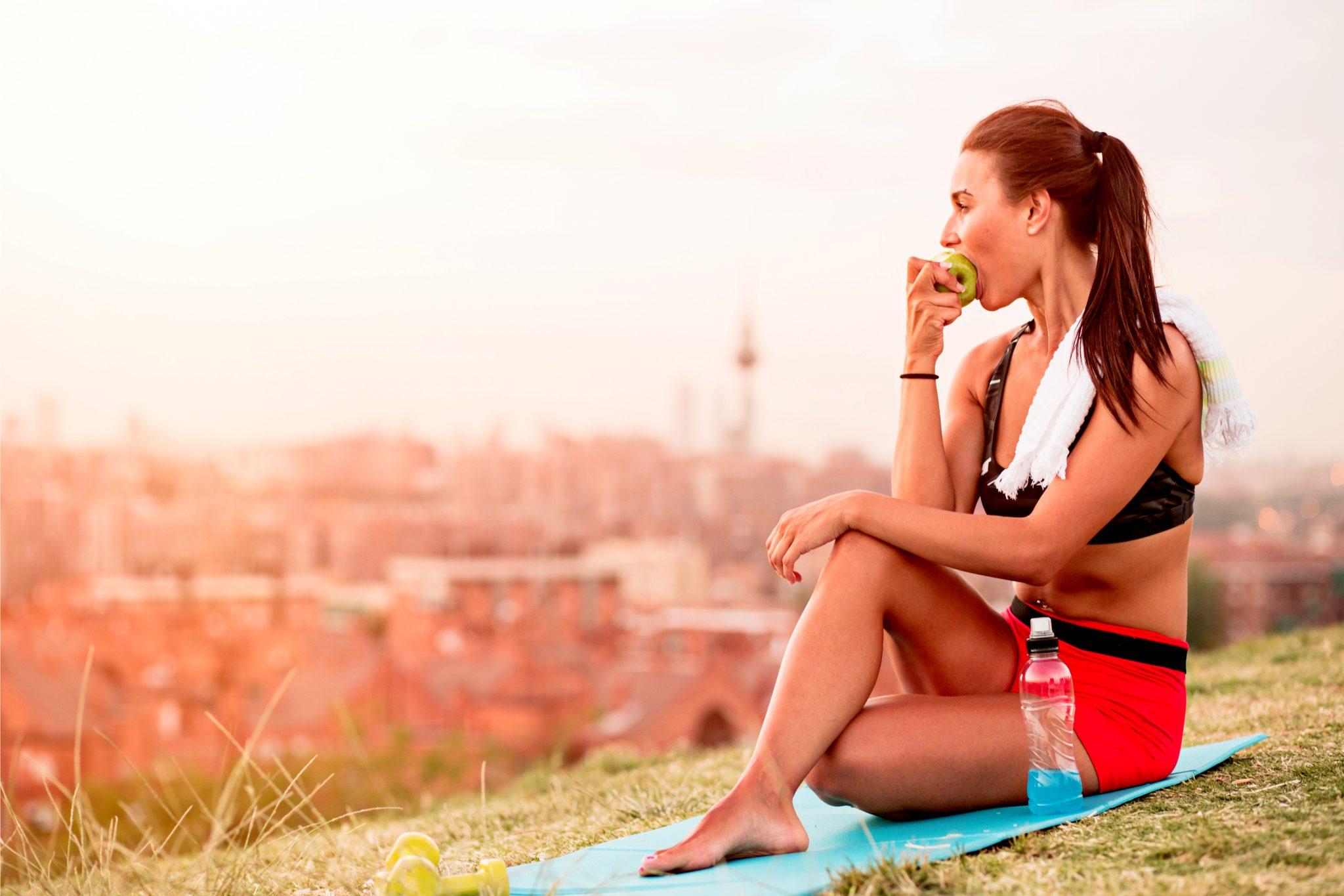 運動後にリンゴを食べている女性