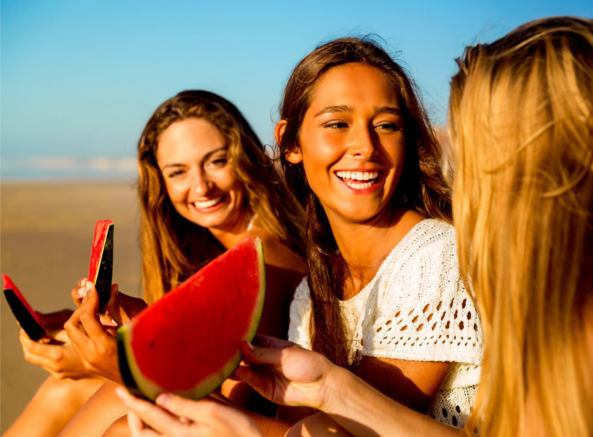 スイカをビーチで食べている美女3人組