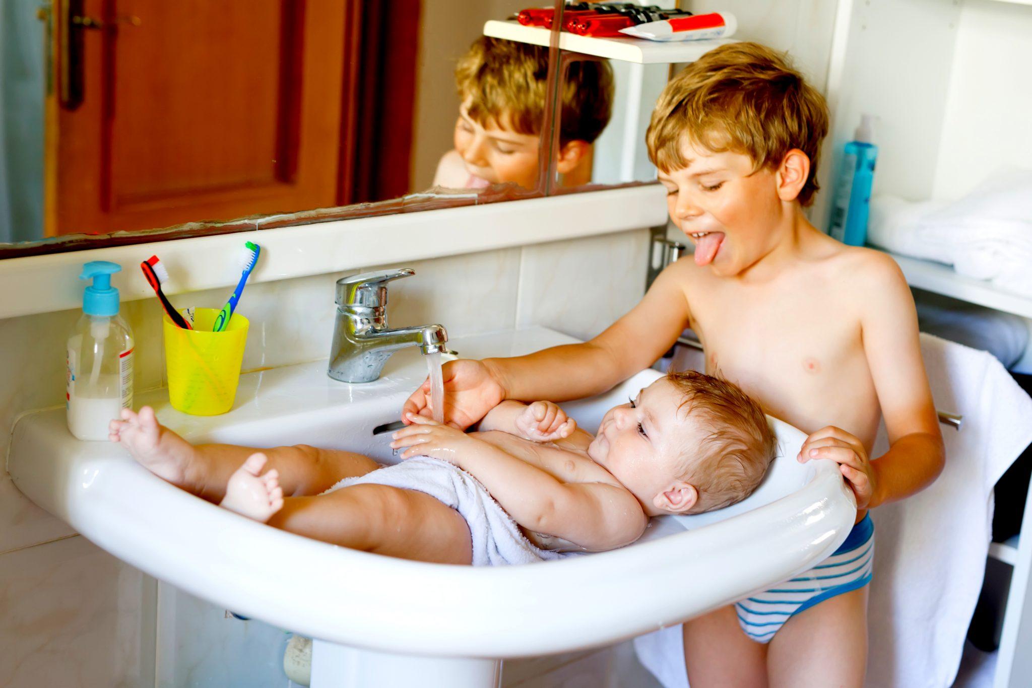 洗面所で手と身体を洗っている子どもたち