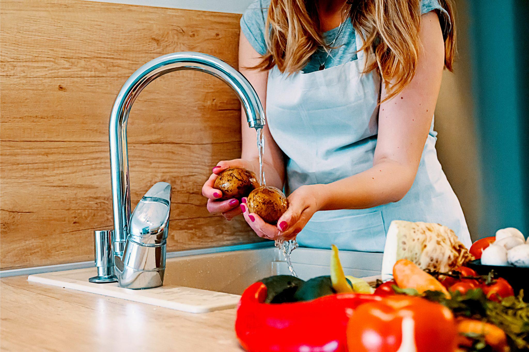 キッチンでジャガイモを洗っている主婦