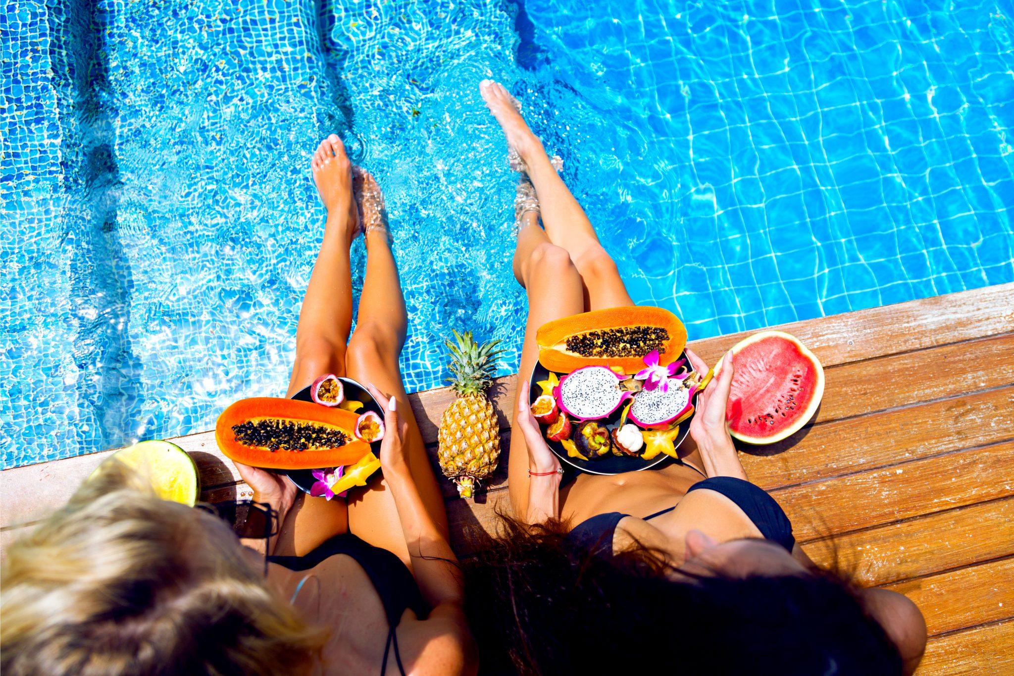 プールサイドで果物を食べている肌のきれいな女性