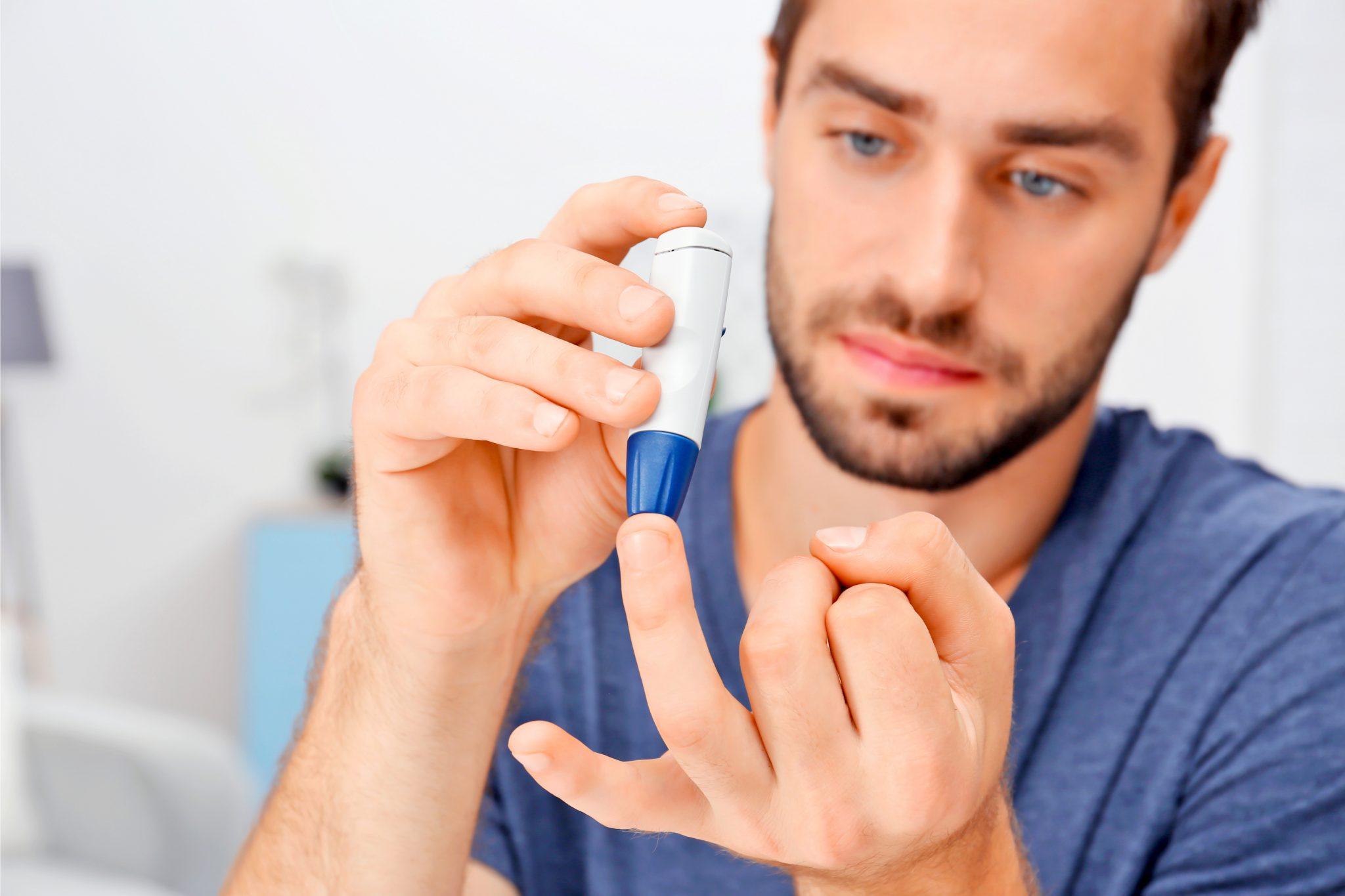 糖尿病患者が指の血液を採取している