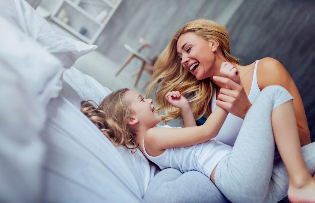 母と娘がベッドでリラックスしながら遊んでいる