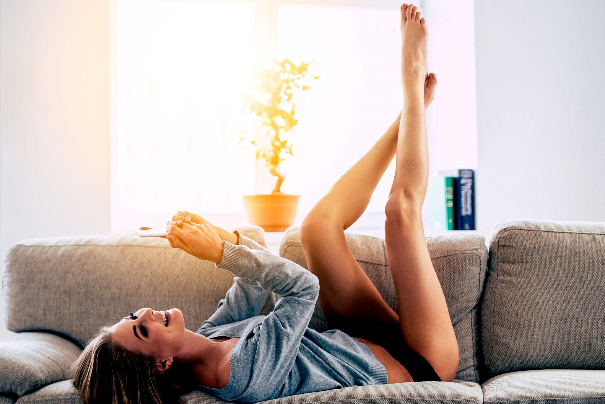 ソファに横になりながら綺麗で長い脚を伸ばしている女性