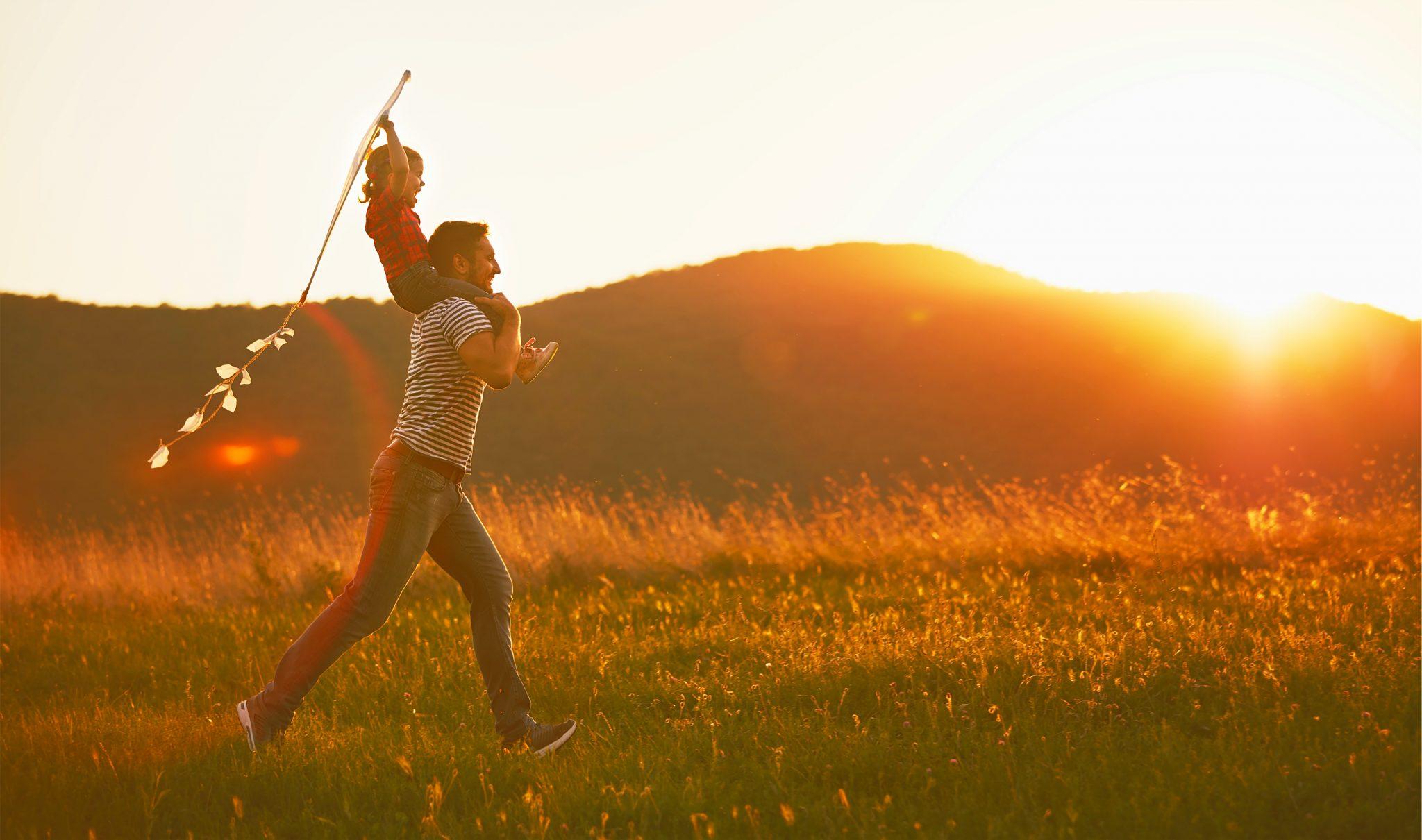 子どもを肩車して芝生を走っているお父さん