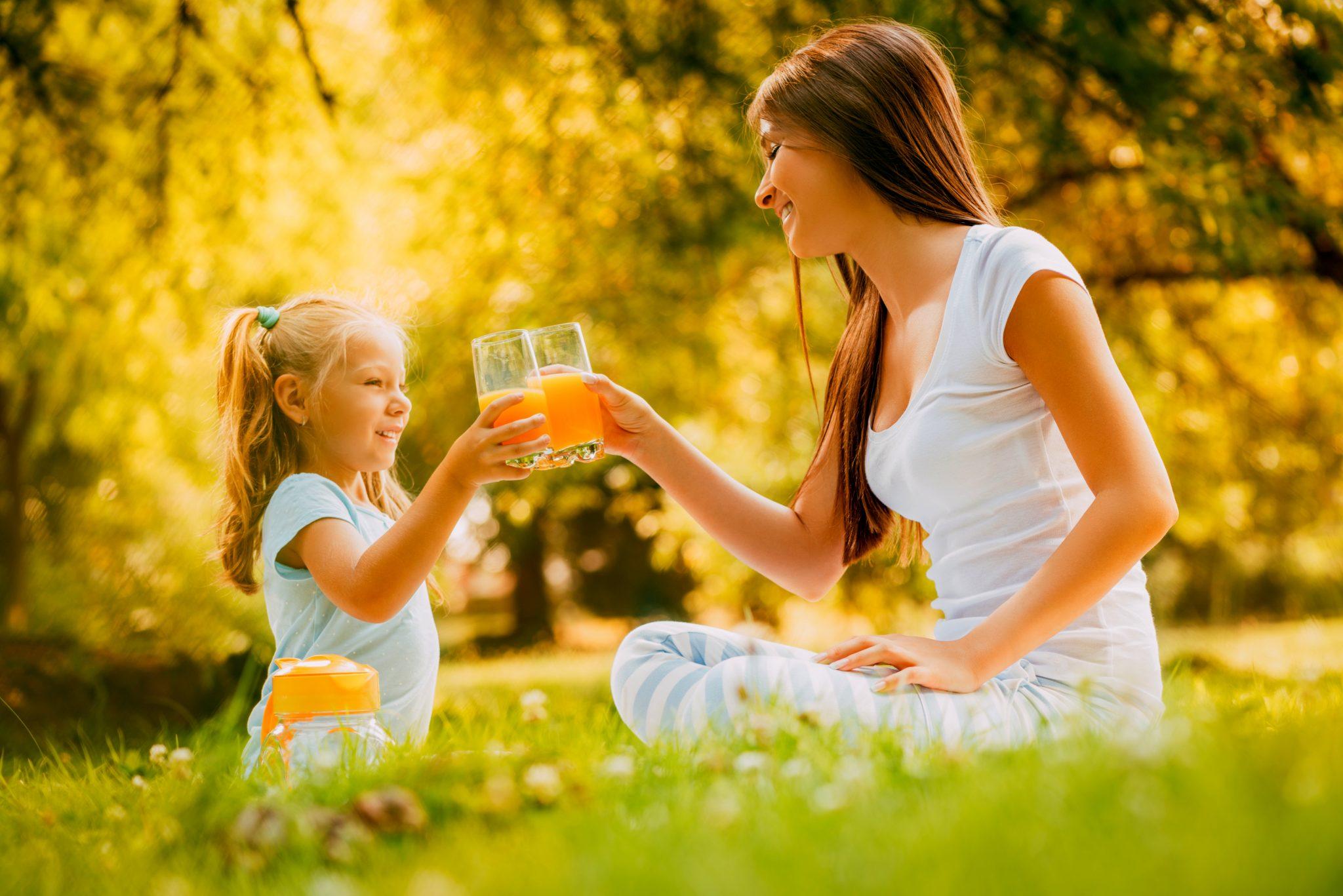 外でお母さんと一緒にオレンジジュースを飲んでいる女の子