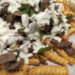 A savory steak, pepper, & onion mixture coated in a creamy, cheesy sauce all resting on a mound of crispy crinkle-cut fries. Philly Cheesesteak Fries can shared with friends at your Super Bowl gathering or, if you're like me, just make them for dinner. | eatatkates.com