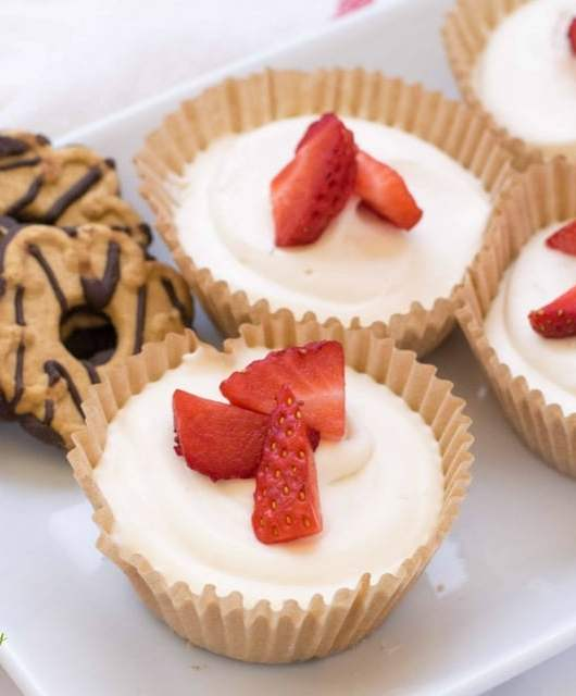 Fudge stripe cookies on a plate with no bake cheesecakes and strawberries