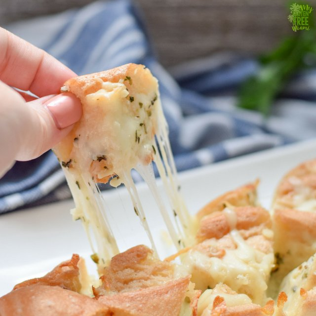 cheese being pulled in gluten free pull apart cheesy bread