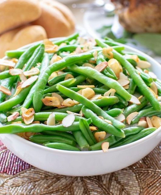 fried garlic and almond green beans on table with side dishes