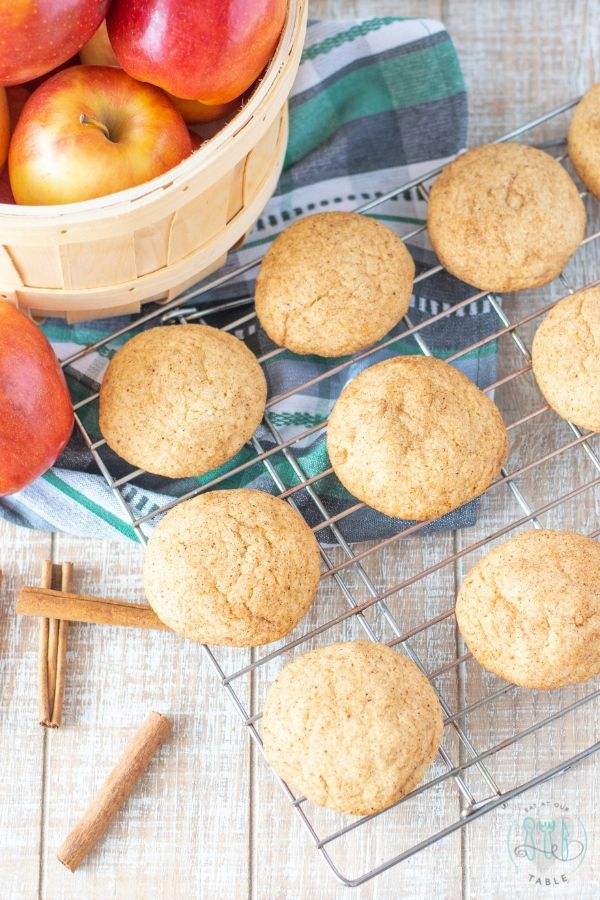 gluten free apple spice snickerdoodles overhead shot on a cooling rack with basket of apples