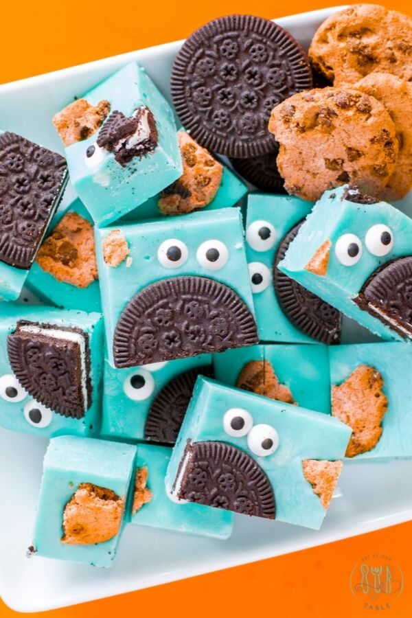 Gluten Free Cookie Monster Fudge on a plate with chocolate creme and chocolate chip cookies.