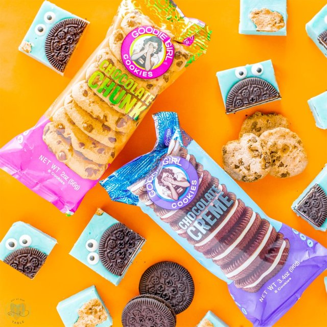 Goodie Girl Cookie snack packs with gluten free cookie monster fudge on orange background.