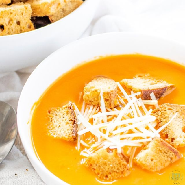 bowl of gluten free tomato soup with garlic butter croutons and parmesan cheese