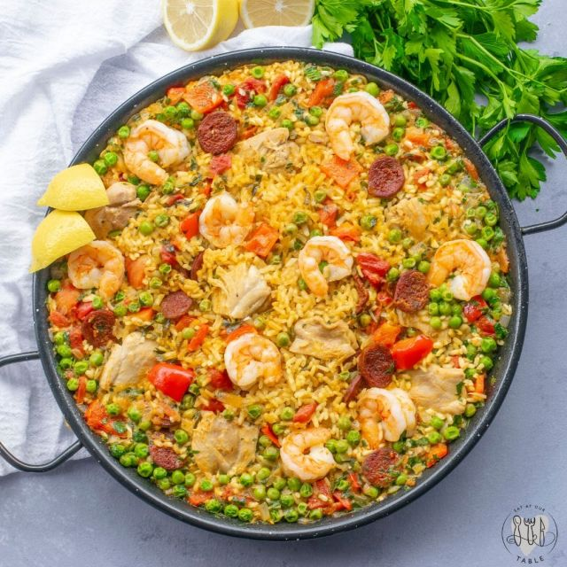 overhead shot off paella mixta in paella pan with parsley
