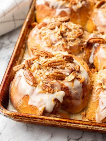 Baked carrot cake cinnamon roll with pecans and coconut on top in a metal pan on marble.