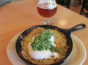 Birdie in a Skillet: Two medium poached eggs, breakfast potatoes, tomatoes, basil pesto, mozzarella, parmesan.