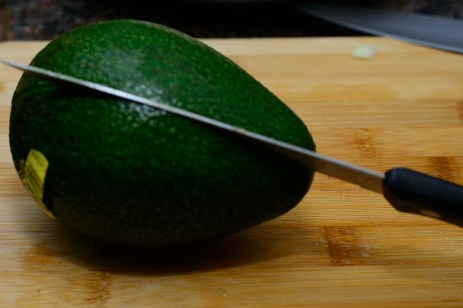 Cut the avocado in half by cutting into it until you reach the stone then run the knife all the way around
