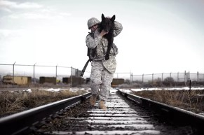soldier carrying a dog