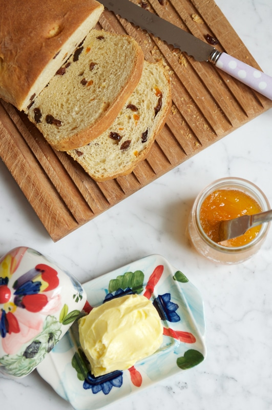 slices of fruit loaf on wooden bread board with butter dish and jar and marmalade