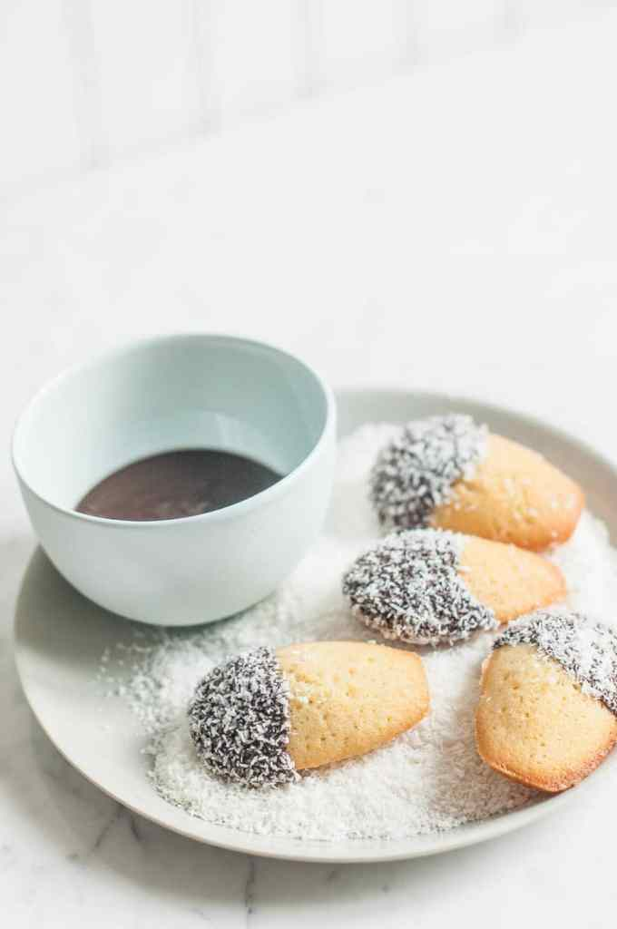 lamington madeleines in bowl of coconut with blue bowl of melted chocolate