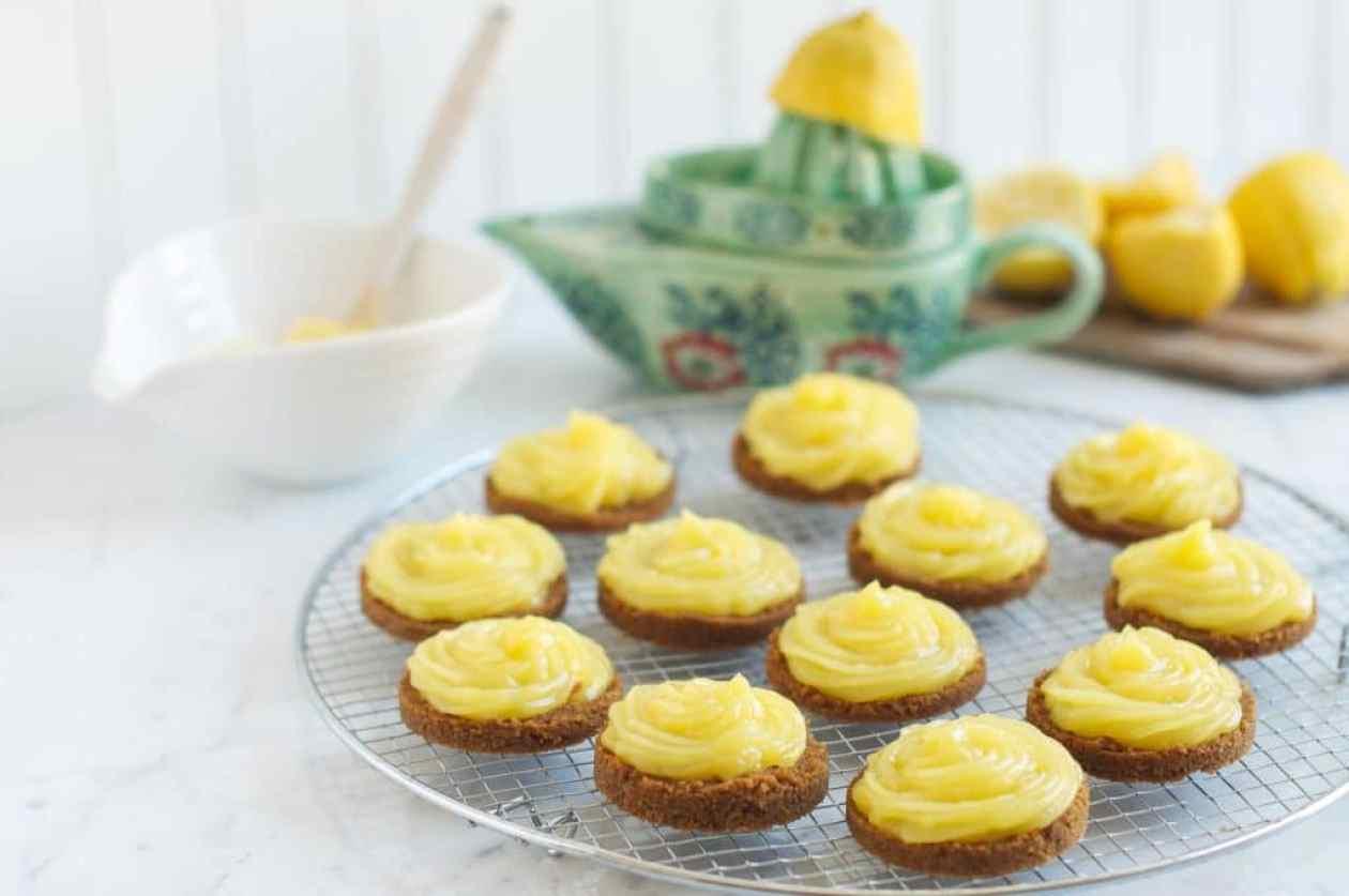 lemon curd tarts on wire rack with green lemon juicer